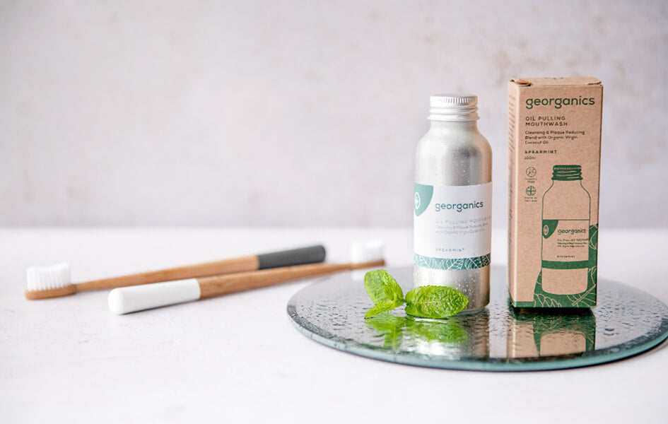 This image shows two bamboo toothbrushes lay down next an aluminium bottle of mouthwash.