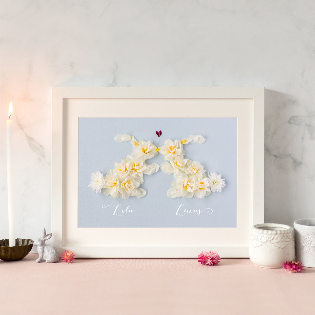 personalised love bunnies print, two yellow bunny rabbits nose to nose on a blue background, made by photographing real daffodils and petals.