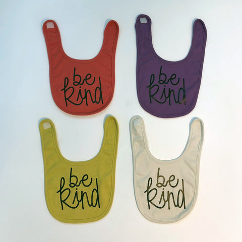 """Be Kind"" bib in 4 colors; mustard, violet, ecru and coral"
