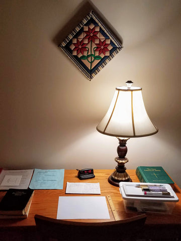Desk with lamp, Bible, paper, and pens