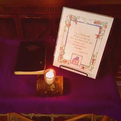 Table with cloth, Bible, prayer card, and candleholder