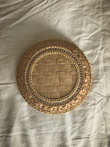Intricately plaited round cane basket