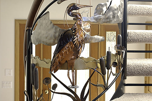 Artistic metal staircase and handrail for a residential home. Decorated with metal animals, plants, and natural features