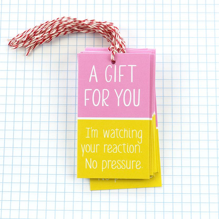 Gift tag with pink box and yellow box on grid paper backdrop