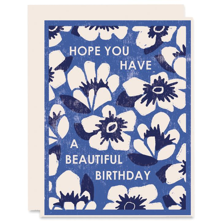Birthday card with blue background and white flowers with dark blue centers