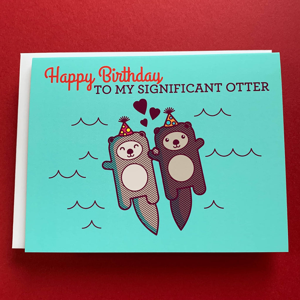 birthday card with two otters holding hands and wearing little birthday party hats