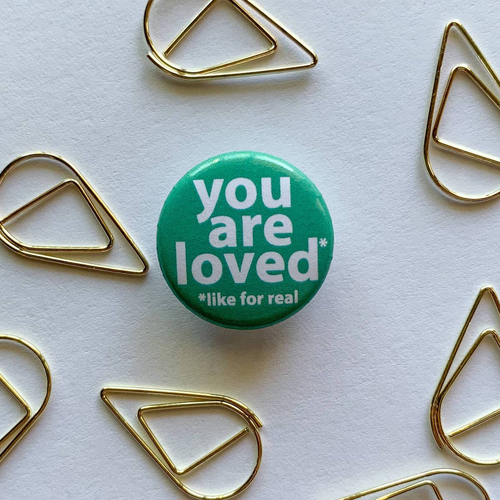 teal button with you are loved in white letters