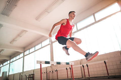 An image of a man jumping over a hurdle.