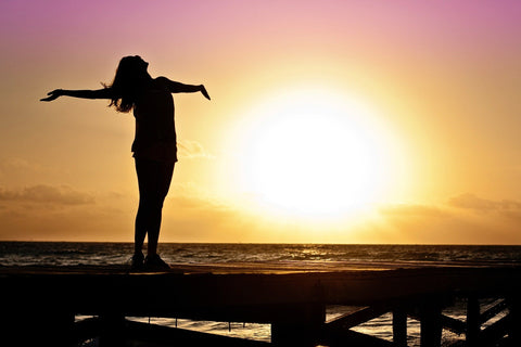 The silhouette of a woman in the sunset spreading her arms in freedom.