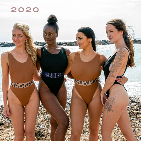 4 women at the beach in orange leopard print and black marble swimsuits