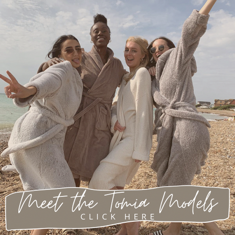 swimwear models at the beach in dressing gowns laughing