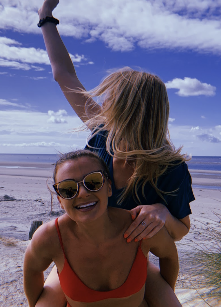 two women at beach in swimwear and gold sunglasses