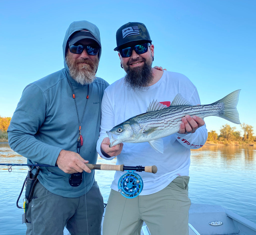 two men holding striped bass