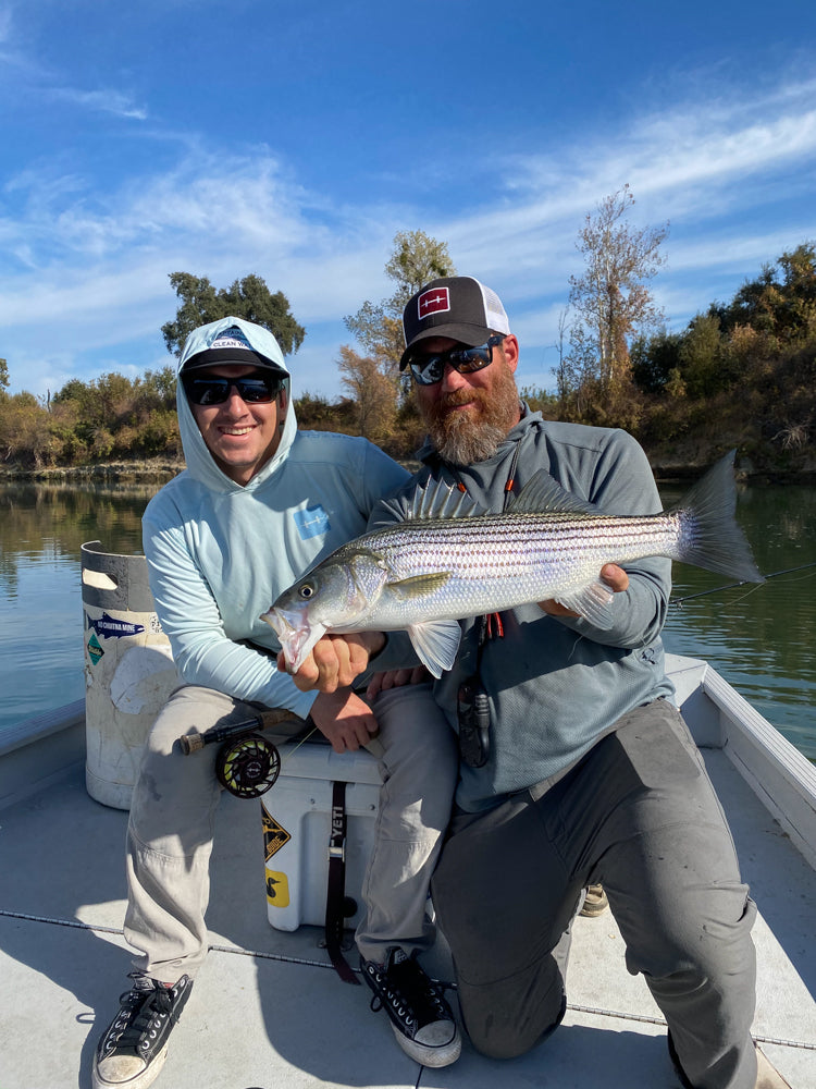 two men on a boat holdind striped bass