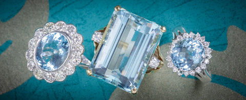 Three Aquamarine Rings on Blue and White Background