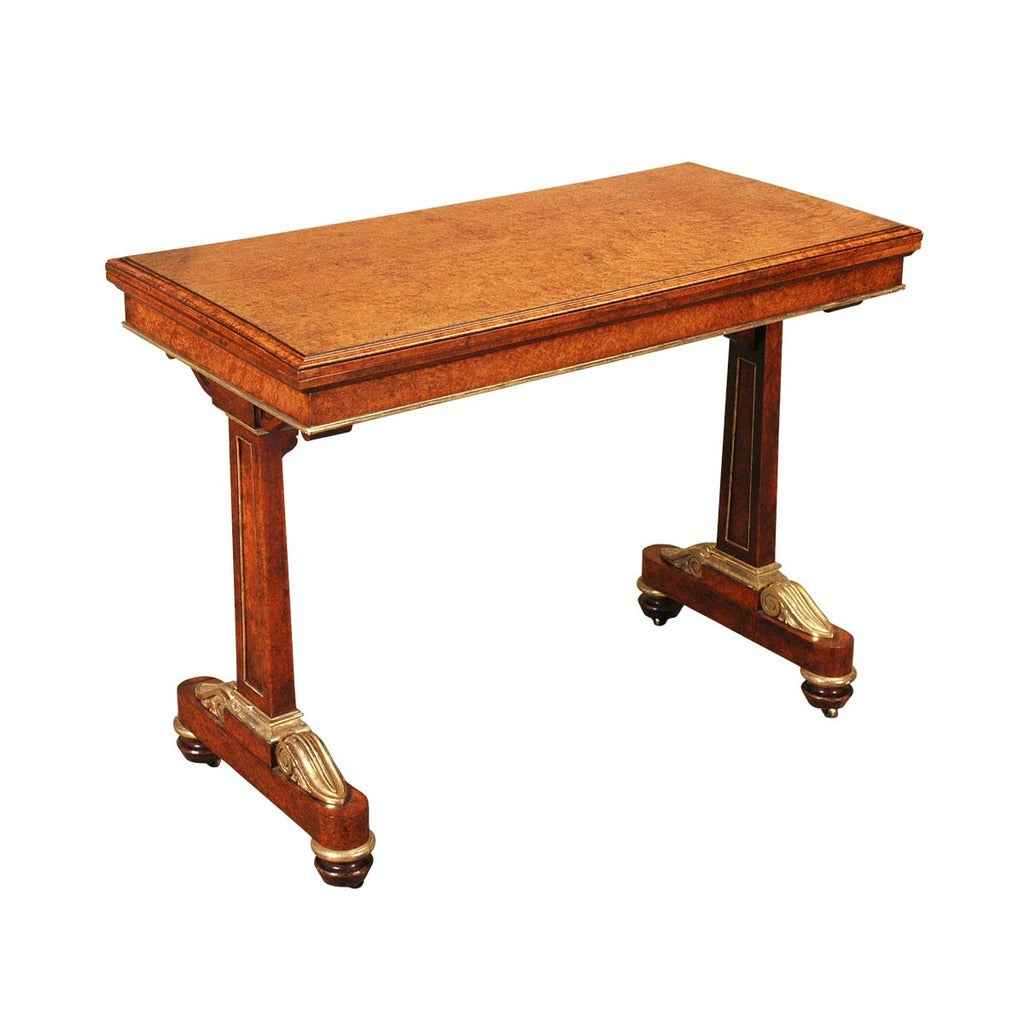 Amboyna card table with gilt accents and recessed castors. View 1