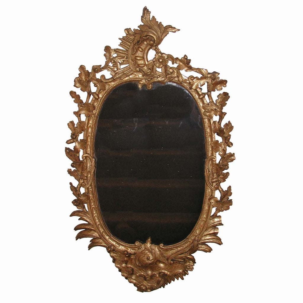 An English carved and gilded oval mirror with acanthus leaf and floral motifs. view 1