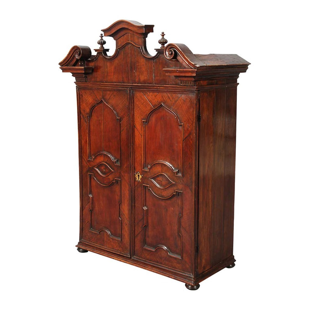 An Italian walnut cabinet with elaborately shaped cornice surmounted by turned finials. view 1