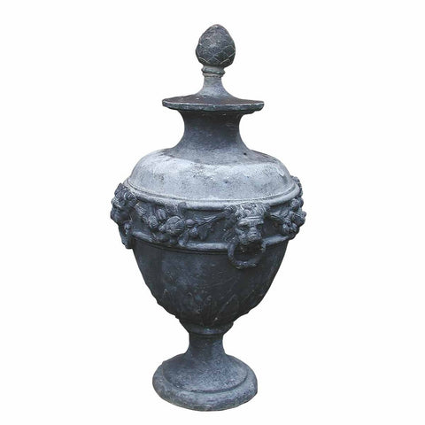 An antique lead urn with lid and adorned with lions' heads and flowers. view 1