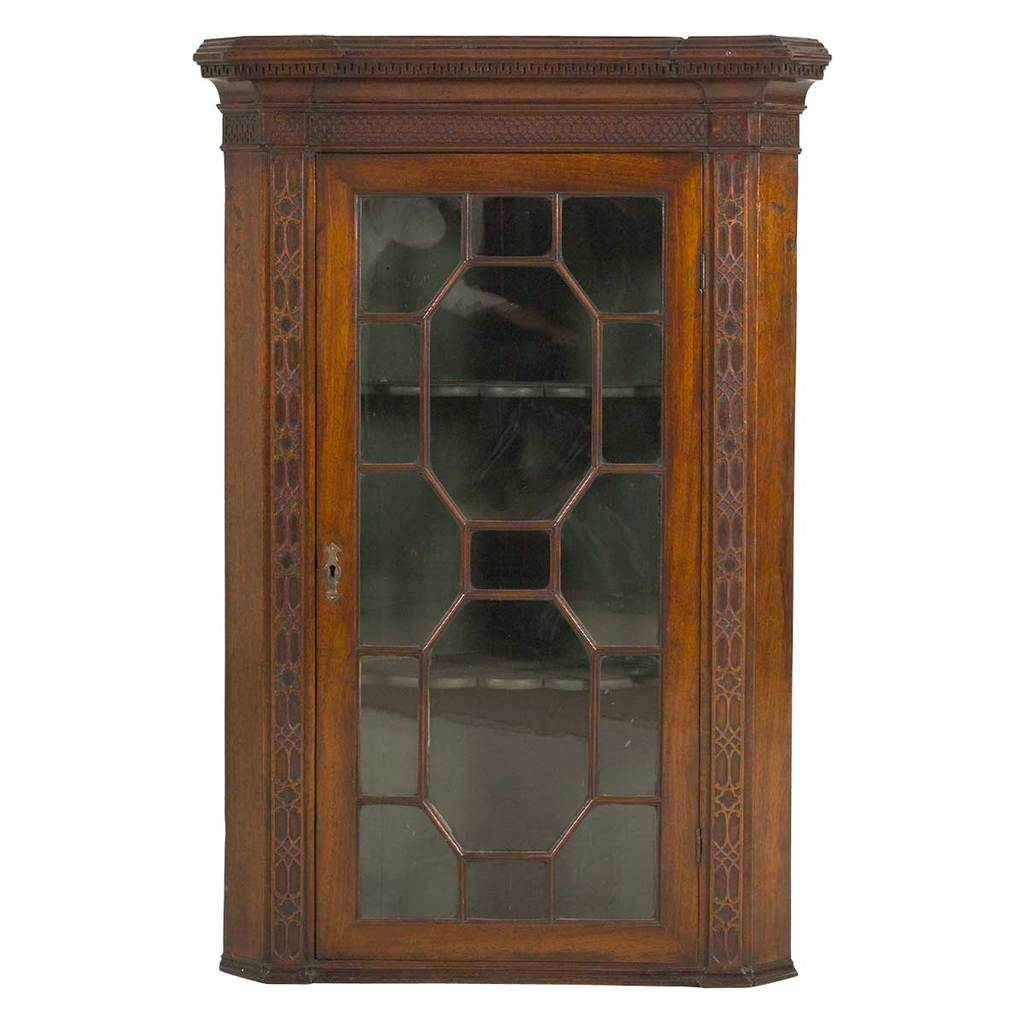 An English mahogany hanging corner cabinet with glazed doors. view 1
