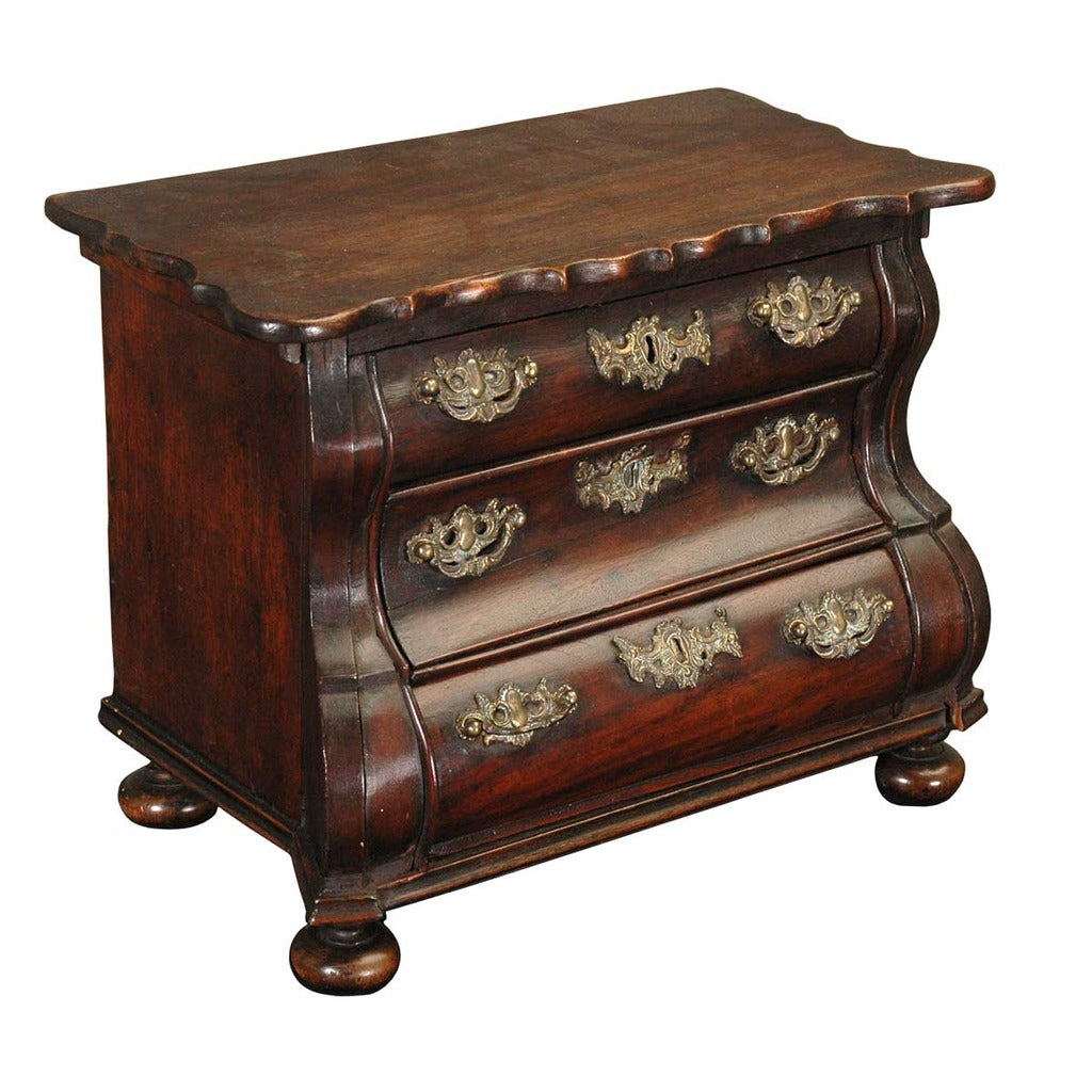 A 18th century mahogany bombe-shaped model chest of drawers on bun feet. view 1