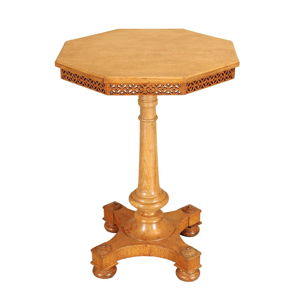 A 19th century oak octagonal lamp table with open fretwork frieze. view 1