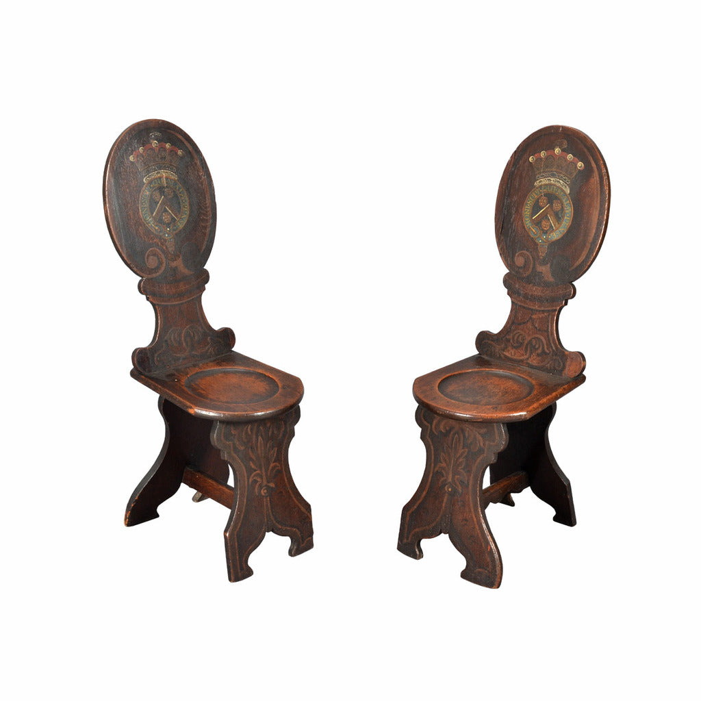 A pair of oak hall chairs; the oval backs painted with an armorial. view 1