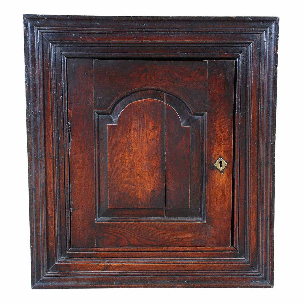 An English oak hanging corner cupboard with an arched, paneled door. view 1