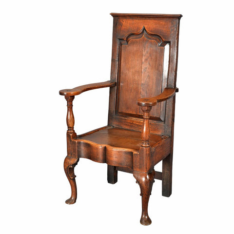 An antique oak wainscot chair with shaped and fielded panel back. view 1
