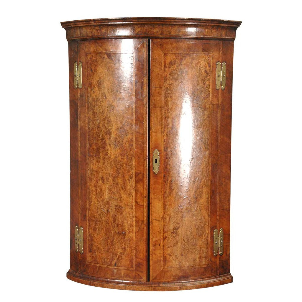 A bow-fronted burl walnut hanging corner cupboard with feather-banding and excellent color. view 1