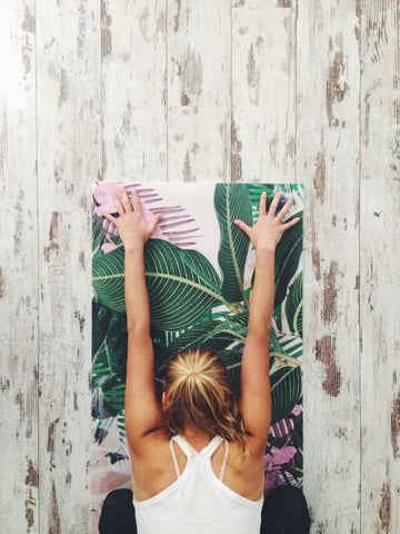 Girl practicing yoga on palm tree mat - O2 Living blog by makers of living health and wellness hemp extract and progesterone