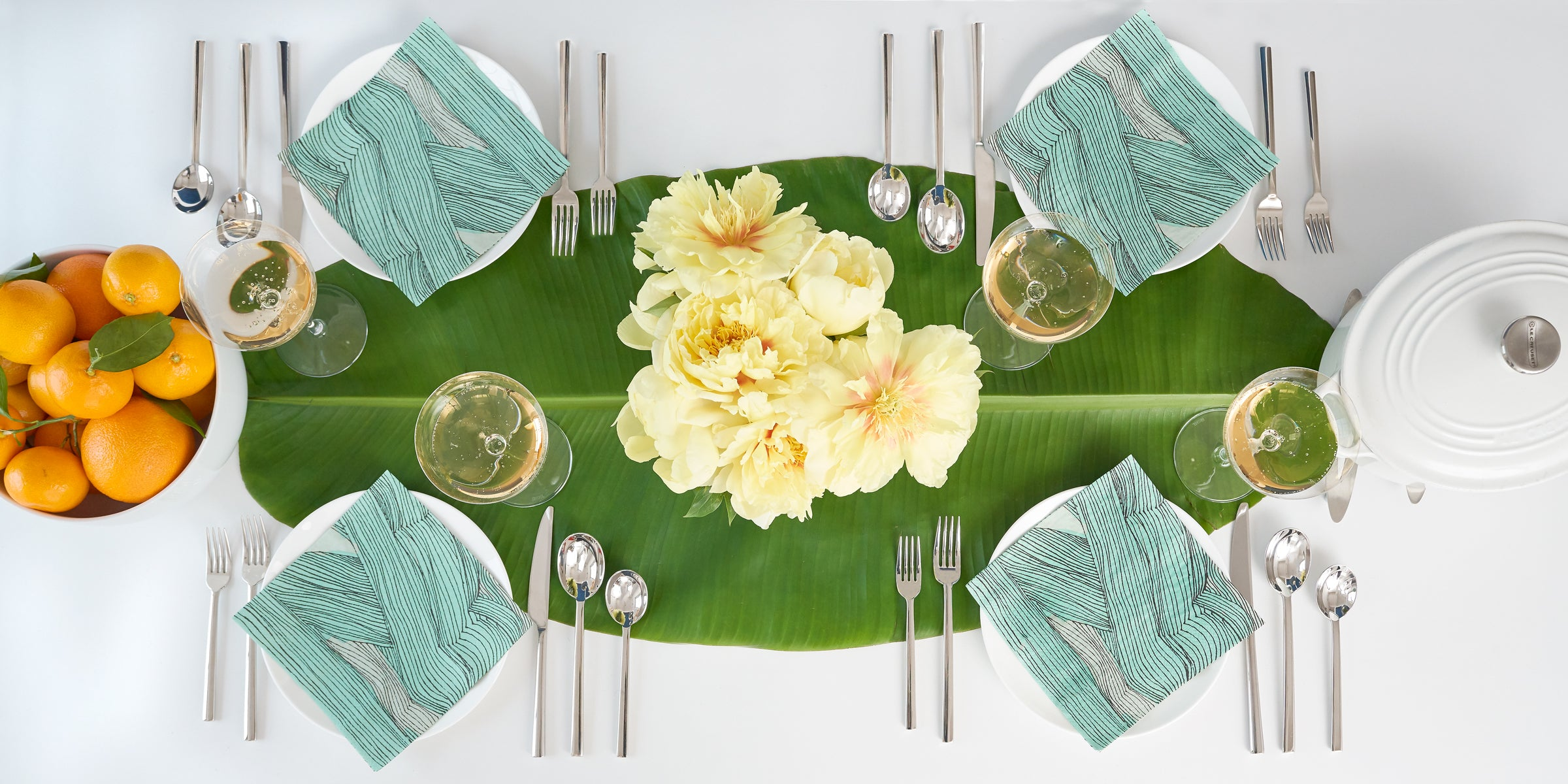 Green, black and off-white dinner napkin with modern abstract pattern in table setting