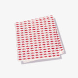 White cocktail napkin with red lightning bolt pattern