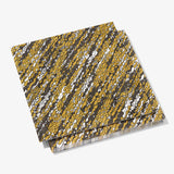 Gold, black and white dinner napkin with abstract pattern