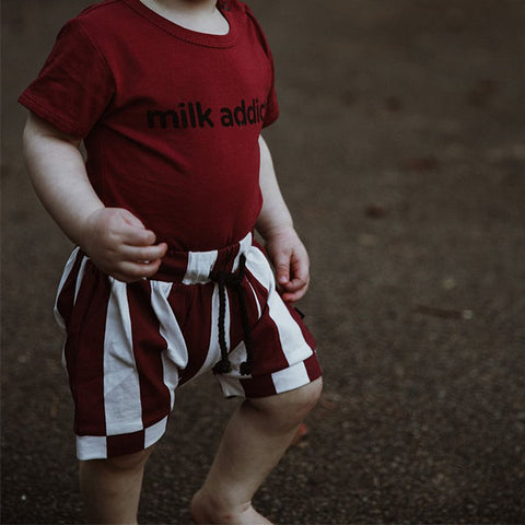 boy wearing Milk Addict Baggy Stripe Shorts - Rust