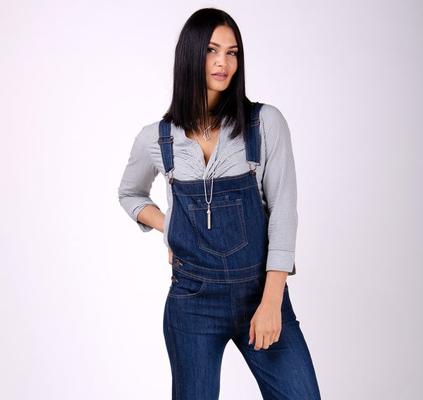 'Dottie' style denim indigo bib-overalls for women, paired with gray blouse.