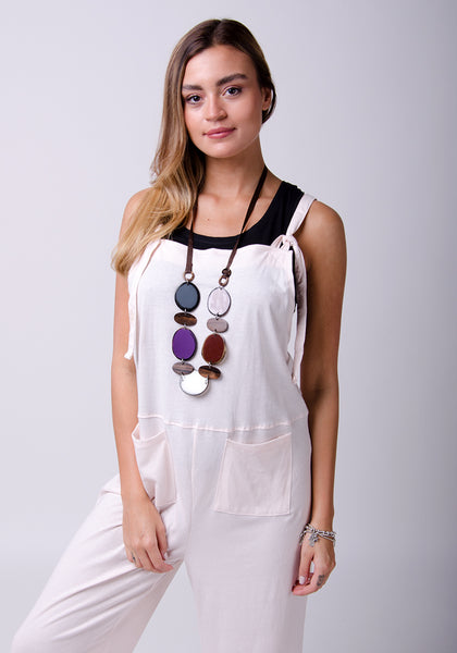 Two-thirds shot wearing pale pink, loose fitting cotton dungarees with black vest and chunky, multi-coloured necklace.