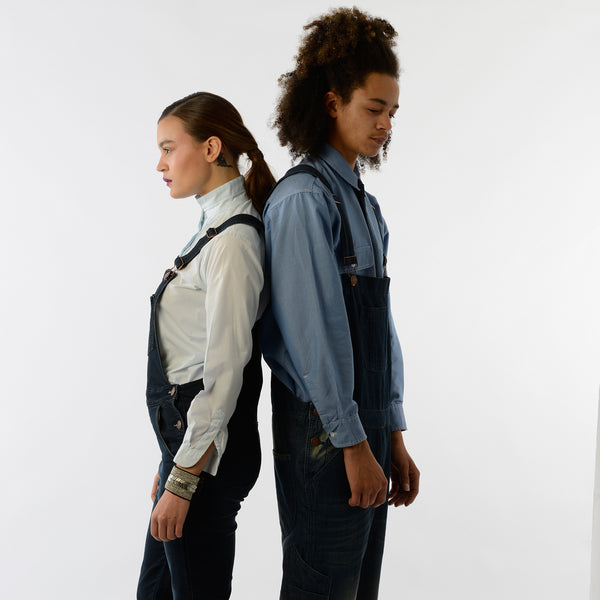 Man and woman standing back-to-back in dark denim overalls.