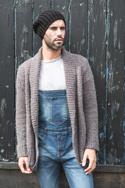 Men's skinny denim overalls paired with wool jacket and hat.