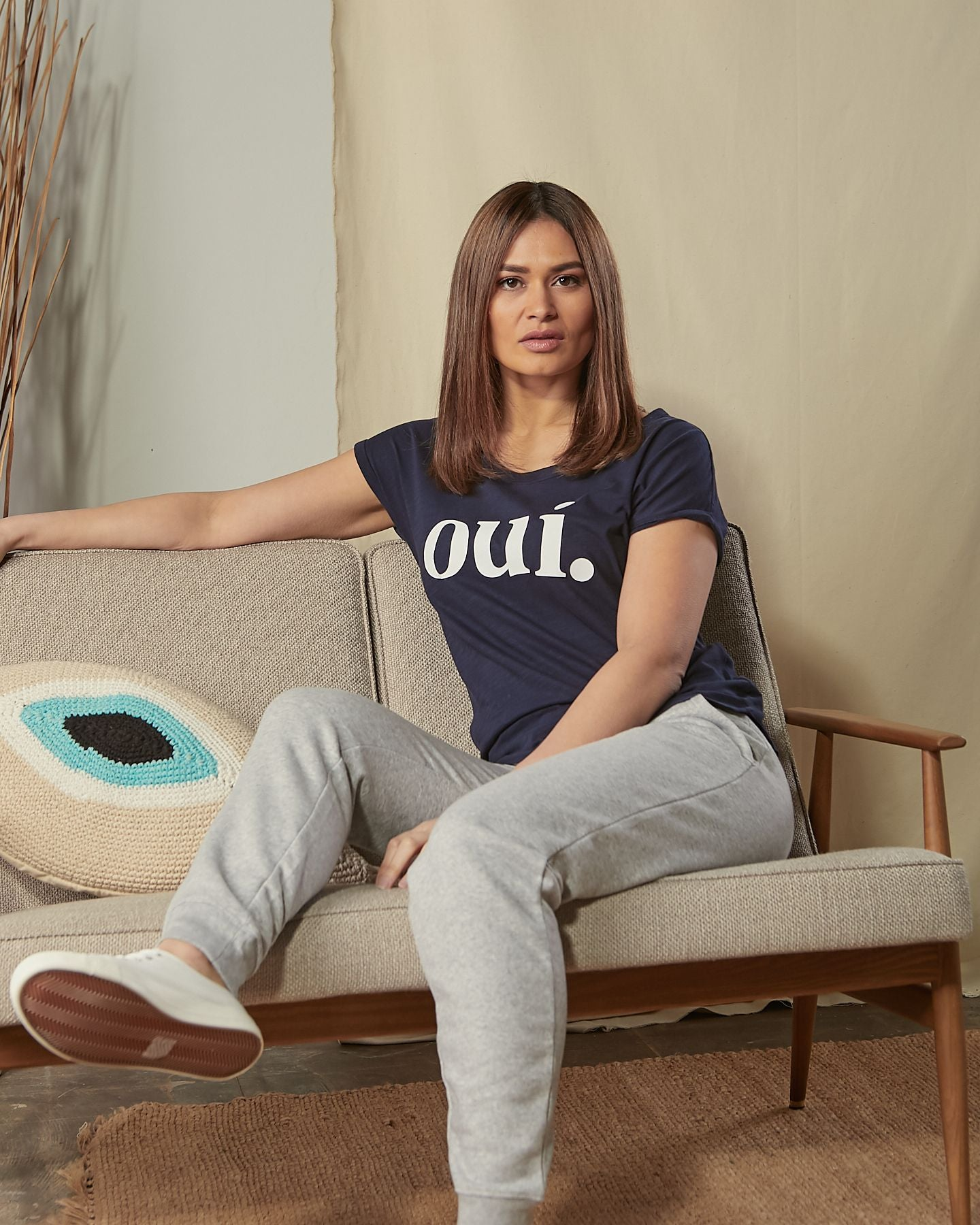 Sitting on sofa wearing blue 'Oui' t-shirt with gray pants.