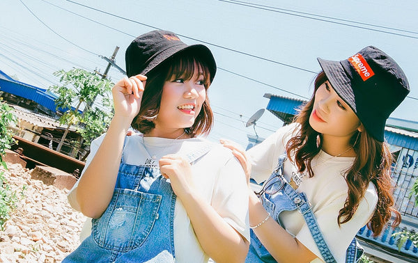 Two young women wearing festival overalls.
