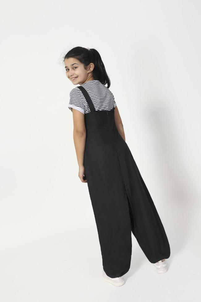 Full rear pose looking over left shoulder, wearing Pumpkin style, wide leg jumpsuit with adjustable button straps.