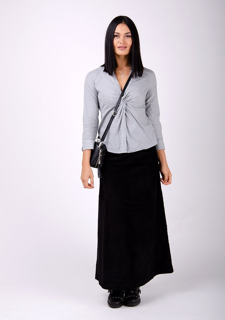 Full-frontal pose facing directly ahead wearing versatile Lottie long black cord skirt.