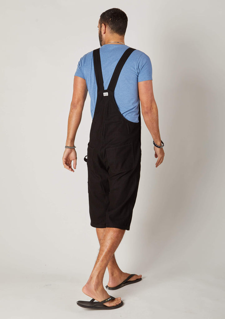 Rear full-length pose men's black bib-overall shorts showing back pockets and Wash Clothing logo label
