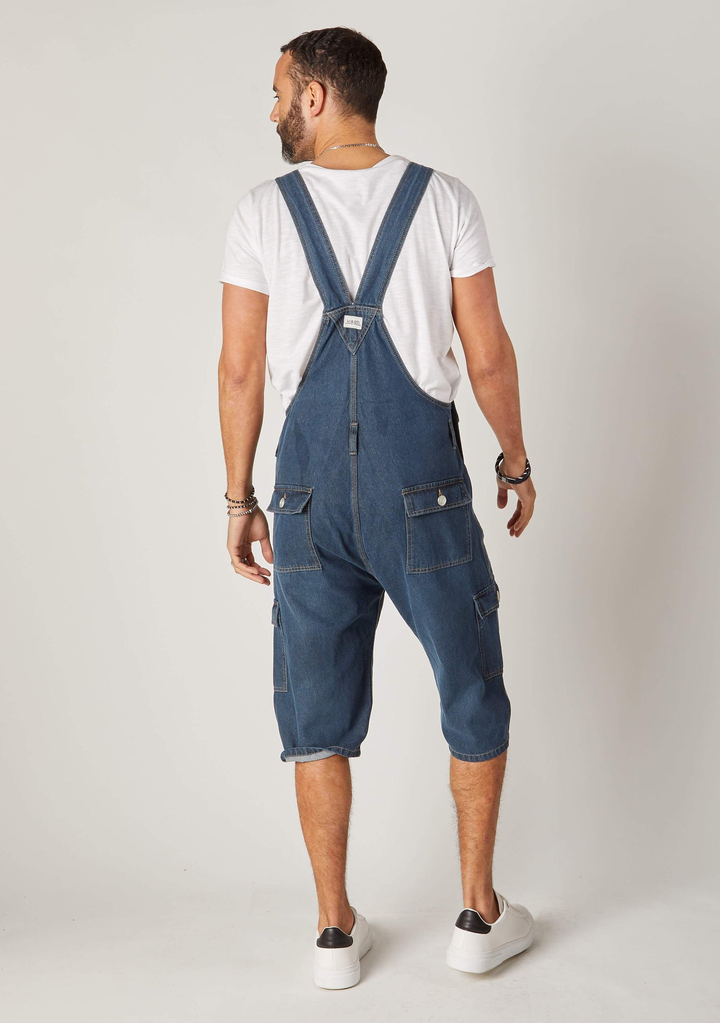 Rear full-length pose men's denim bib-overall cargo shorts showing back pockets and Wash Clothing logo label