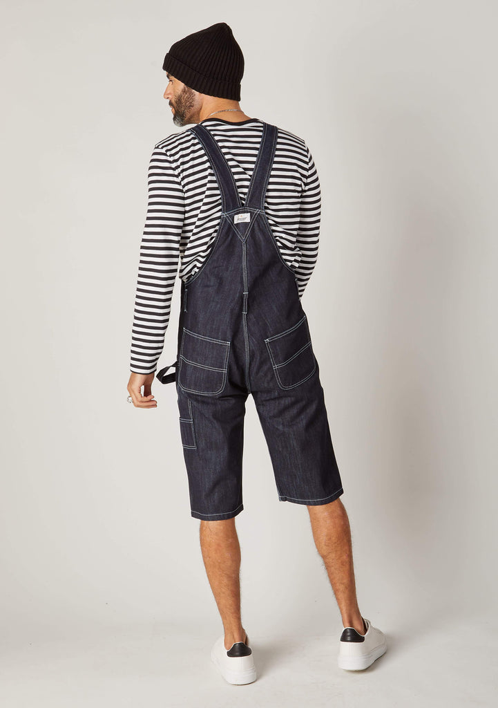 Rear full-length pose men's denim bib-overall shorts showing back pockets and Wash Clothing logo label