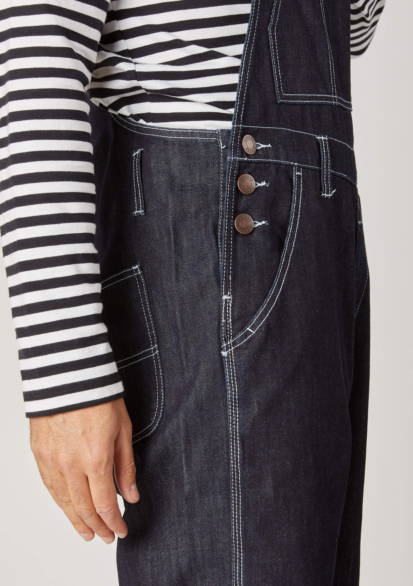 Close-up of Chet Dark Blue Denim Overall shorts for men showing the side three button fastening and contrast stitching