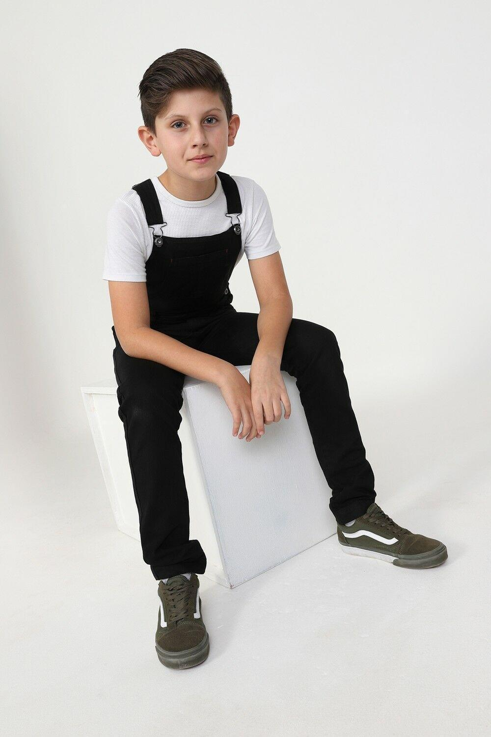 Boy sitting on box wearing durable zip fly, machine washable bib-overalls.