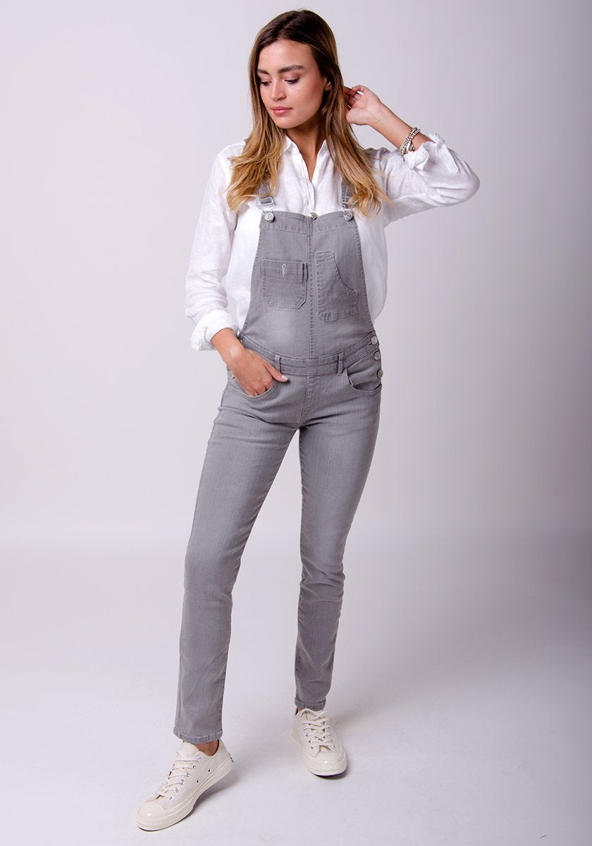 Classic frontal pose with hand in right front pocket, wearing faded grey, close cut grunge-style dungarees.