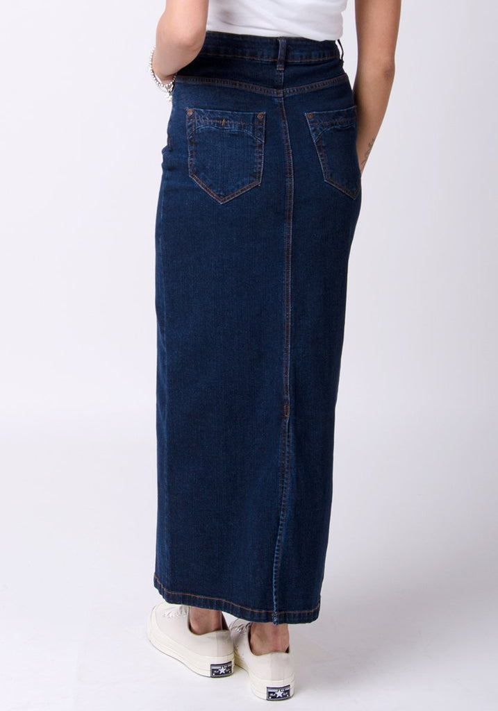 Half-rear pose showing back split and pockets of darkwash, practical denim skirt.